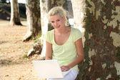 Jovem mulher a trabalhar no seu laptop no parque — Fotografia Stock