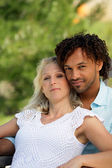 Mixed race couple relaxing in park — Stock Photo