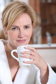 A young woman wearing a dressing gown, holding a mug and looking at us. — Stock Photo
