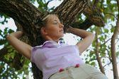 Mujer apoyado contra un árbol — Foto de Stock