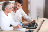 Young man helping senior woman buy online — Stockfoto
