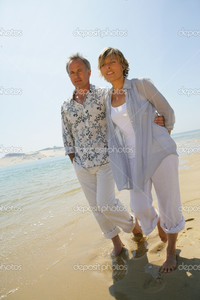 Romantic couple walking barefoot along a beach  Stock Photo #9179763