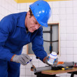 Stock Photo: Plumber applying glue to a grey plastic pipe
