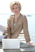 Woman on laptop by the sea — Stock Photo
