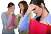Two female colleagues mocking a woman in trouble — Stock Photo