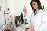 Kvinna i laboratorium med en flaska vin och pipett — Stockfoto