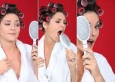Brunette wearing bathrobe with hair curlers holding hairbrush holding agai — Stock Photo