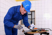 Plumber applying glue to a grey plastic pipe — Stock Photo