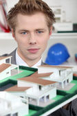 Young architect posing with model — Stock Photo