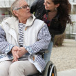 Young woman helping a senior in a wheelchair — Foto de Stock