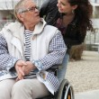 Young woman helping a senior in a wheelchair — Stock Photo #9198511