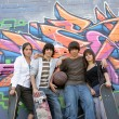 Teenagers posing in front of tagged wall — Stock Photo #9198582