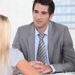Man sat at desk talking to blond female — Stock Photo