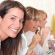 Three young women brushing their teeth — Stock Photo #9199598