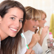 Three young women brushing their teeth — Stock Photo
