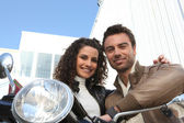 Urban couple on a moped — Stock Photo