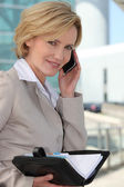 Businesswoman checking her diary smiling — Stock Photo