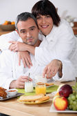 Couple at breakfast in bathrobes — Stock Photo