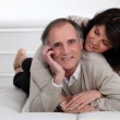 Mature couple lying in bed showing their affection — Stock Photo