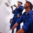 Electricians installing circuit breaker - Stock Photo