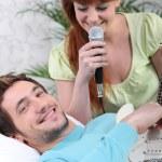 bir adam gitar ve bir kadının evde şarkı çalma — Stok fotoğraf
