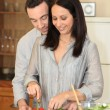 Couple cutting vegetables in a kitchen - Stock Photo