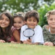 Kids playing with magnifying glass in park — Stock Photo #9207891