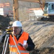 Surveyor on a building site - Stock Photo