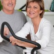 Man and woman doing cross trainer — Stock Photo