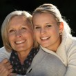 Young woman hugging her grandmother — Stock Photo