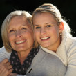 Young woman hugging her grandmother - Stock Photo
