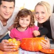 A family carving a pumpkin.