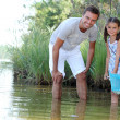 A daughter and her father fishing in a river — Stock Photo