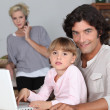 Family in kitchen with laptop — Stock Photo