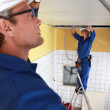 Laborers installing piping in ceiling — Stock Photo