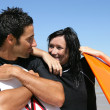 Couple stood at the beach in wet-suits waiting to surf — Stock Photo