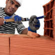 Stock Photo: Mason carving bricks