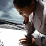 Businesswoman using laptop on her car bonnet — Stock Photo
