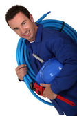 Laborer with a roll on shoulder — Stock Photo