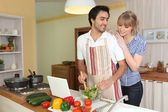 Young man making a salad with his partner — Stock Photo