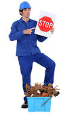 Man stood holding stop sign by crate of refuge — Stock Photo