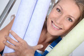 Woman with rolls of wallpaper — Stock Photo