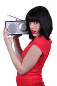 Lady in red listening to a radio — Stock Photo