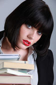 Brunette woman with stack of books — ストック写真