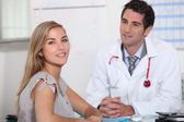 Young female patient consulting with her doctor — Stock Photo