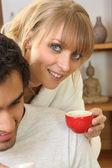 Woman drinking coffee next to husband — Stock Photo