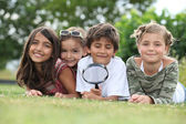 Kids playing with magnifying glass in park — Stock Photo