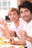 Two young men eating a meal — Stock Photo