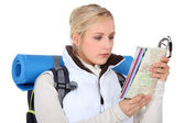 Backpacker with a map and compass — Stock Photo