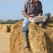 Stock Photo: Farmer with laptop on haystack